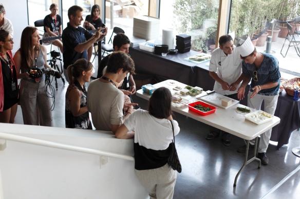 En el back satge un modelo entretiene a Staf y modelos quitandole el sitio al cocinero.